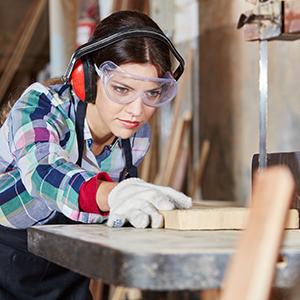 Junge Frau beim Holz sägen während ihrer Ausbildung in einer Schreinerei